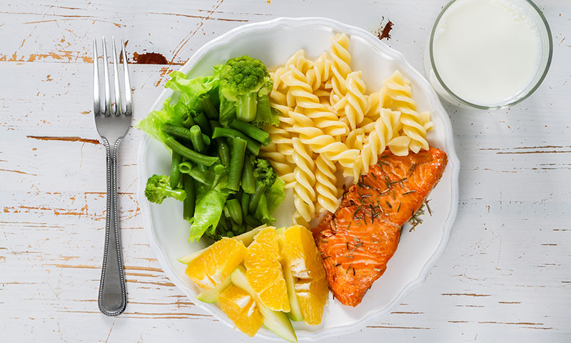 Healthy portioned plate with salmon,pasta, greens, fruits and milk