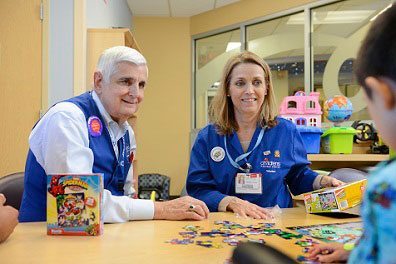 volunteers working on puzzle with little boy inpatient