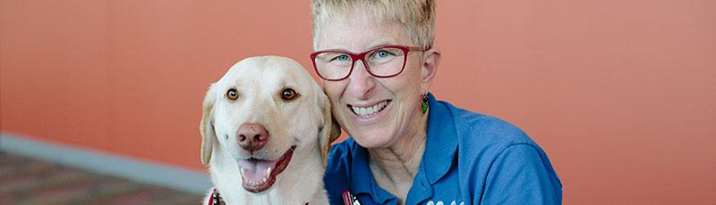 Voluntaria posando con un perro de terapia