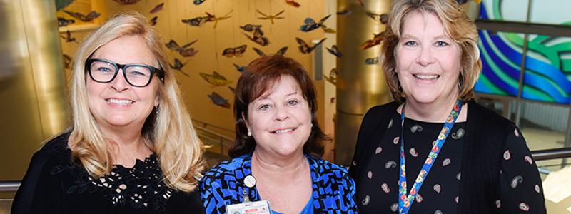 Jenny S. (trabajadora social clínica), Catherine S. (líder del equipo de Trabajo Social) y Laurie W. (administradora de Trabajo Social) posan en el atrio Butterfly