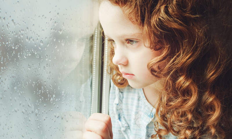 Little girl look out a window on a cold day