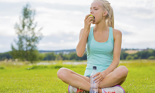 Teenage girl eating apple after a run while sitting in the grass