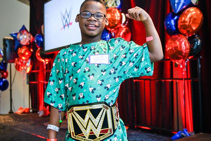 niño pequeño mostrando su fuerza con un cinturón de campeonato