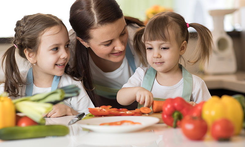 Little girls cooking and eating with their mom